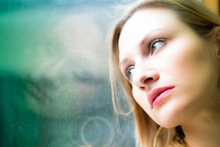 sad people: Beautiful woman standing by a window looking outside