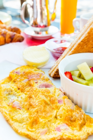 Breakfast -omelet with ham tomato and green salad photo