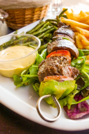 tasty grilled meat and vegetables skewers on a slate plate  photo