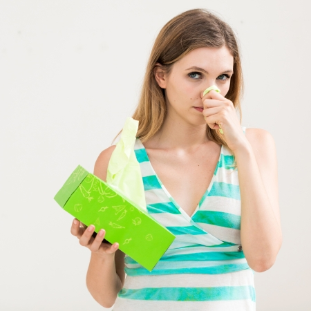 sick woman using tissue on white background photo