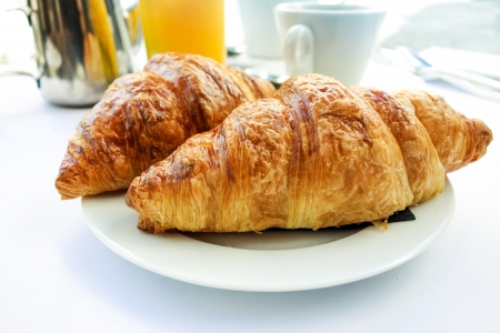 Breakfast with coffee and croissants on table photo