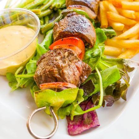 tasty grilled meat and vegetables skewers on plate  photo