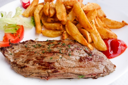 juicy steak beef meat with tomato and potatoes photo