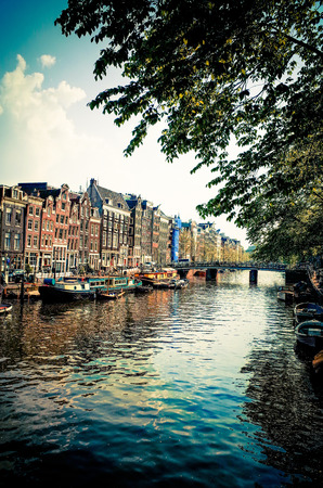 Amsterdam, Netherlands -APRIL 23  Amsterdam canals on April 23, 2014  Beautiful view of Amsterdam canals with bridge and typical dutch houses  photo