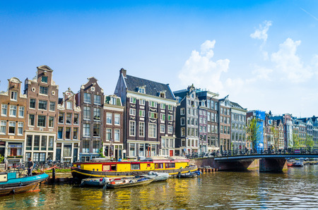 Amsterdam, Netherlands.-APRIL 23: Amsterdam canals on April 23, 2014. Beautiful view of Amsterdam canals with bridge and typical dutch houses.
