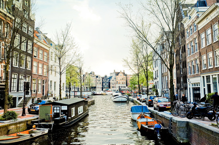 dutch typical: Amsterdam, Netherlands.-APRIL 23: Amsterdam canals on April 23, 2014. Beautiful view of Amsterdam canals with bridge and typical dutch houses.