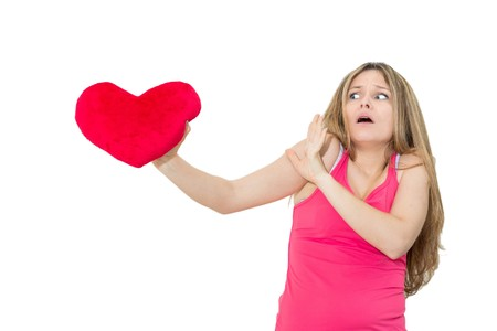 unsatisfied: young lonely sad woman holding red valentine heart Stock Photo