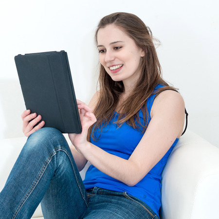 Smiling young woman on the couch with her tablet photo
