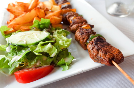 meat dish: tasty grilled meat and vegetables skewers on a slate plate