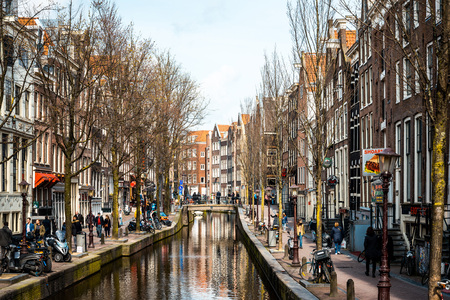 dutch typical: Amsterdam, Netherlands - March 31, 2016 : Beautiful view of Amsterdam canals with bridge and typical dutch houses. Amsterdam, Netherlands