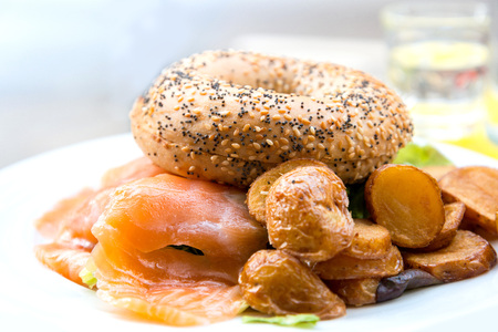 Bagel with fresh cheese and fresh lettuce on table