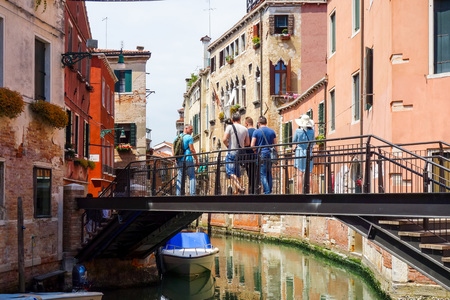 foot bridges: VENICE, ITALY - May 18, 2017.Tourists foot Street in Venice. its entirety is listed as a World Heritage Site, along with its lagoon. VENICE, ITALY.