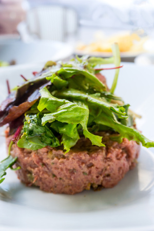 cucumbers: tasty Steak tartare (Raw beef) - classic steak tartare on white plate