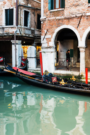 VENICE,ITALY- December 21, 2017 : Tourists on water street with Gondola in Venice. its entirety is listed as a World Heritage Site, along with its lagoon
