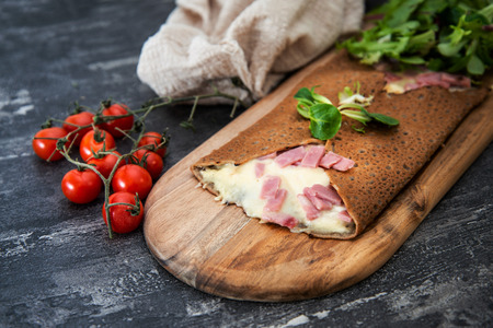 Black wheat and wheat galette topped with cooked ham and emmental cheese Foto de archivo - 99299378