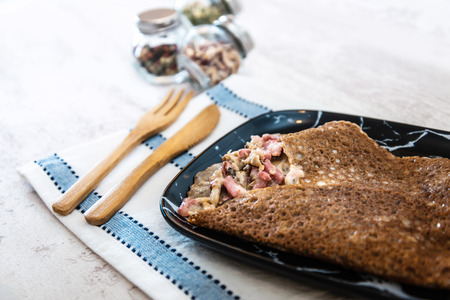 Black wheat and wheat galette topped with cooked ham and emmental cheese 스톡 콘텐츠