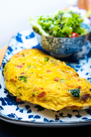 omelet with ham tomato and green salad Imagens