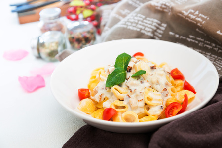 Cooked pasta with a cream sauce and roasted chicken cured with emmental.