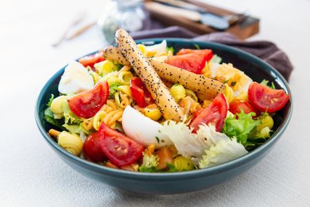 Salad of pasta, egg, smoked salmon tartare, salad and tomato, with a citrus vinaigrette sauce.