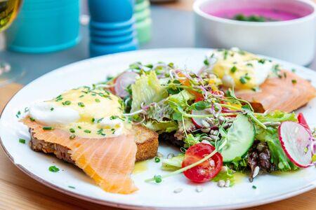 Deux délicieux œufs pochés avec du saumon sur du pain grillé servis avec des légumes mélangés et de la laitue dans une assiette en céramique blanche