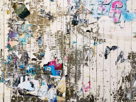 Schichten alter bunter Poster an der Wand, die durch die Zeit für Ihr Grunge-Design beschädigt wurden damaged Standard-Bild