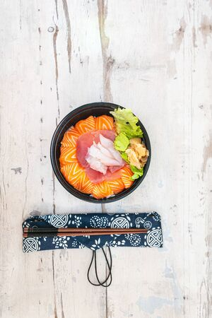 Japanese Chirashi made with assortment of three raw fishes, salmon, tuna and cod fish served on white vinegary rice with Wasabi sauce and ginger slices on top in a bowl.