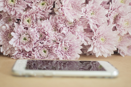 mobile phone with pink flowers background. selective focus Stock Photo