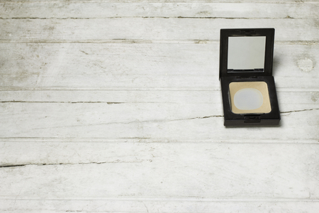cosmetologist: Used Compact pressed powder on white wooden background Stock Photo