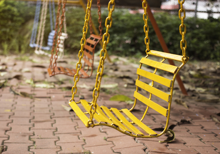 chain swing ride: Empty chain swings in playground with vintage filter Stock Photo