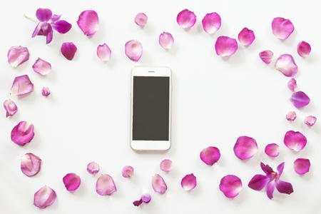 comunicacion oral: marco de pétalos de rosa rosa con teléfono inteligente sobre fondo blanco. vista superior.