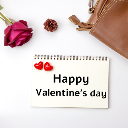 Happy Valentine's day word on notebook background with rose flower and leather bag.