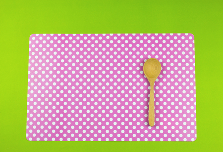 Wooden spoon put on a white polka dots pink place Mat on green background. Stock Photo