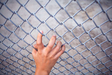 convicts: Man hand grabbing steel mesh cage. no freedom. Top view. Stock Photo