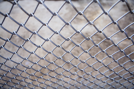 wire mesh: metal fence with concrete background. Stock Photo