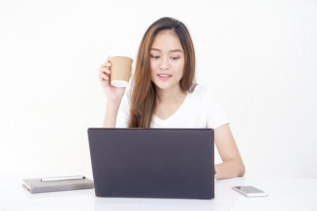 Young beautiful Asian woman drinking coffee and looking at laptop screen. Фото со стока