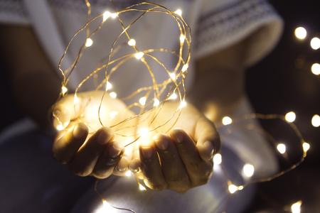 Vrouwenhanden die koord van lichten in dark houden om een wens te maken. Stockfoto