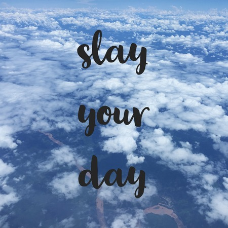 Inspirational motivational travel quote slay your day on sky background.