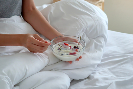 Woman having a bowl of yogurt with fresh fruits in bed.
