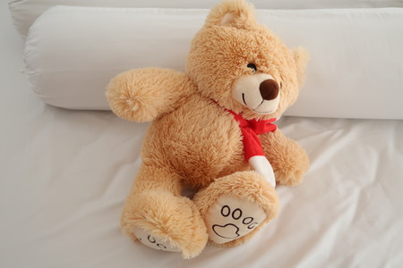 Teddy bear laying on white bed. Stock Photo