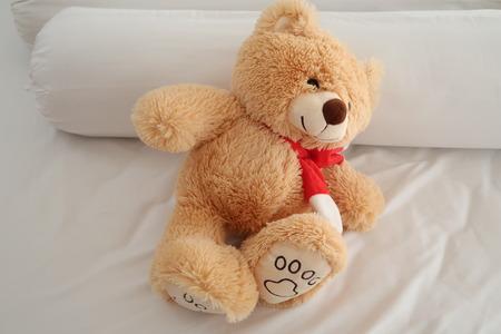 Teddy bear laying on white bed. Фото со стока