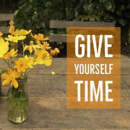 nspirational motivational quote give yourself time on wooden table with flowers vase background.