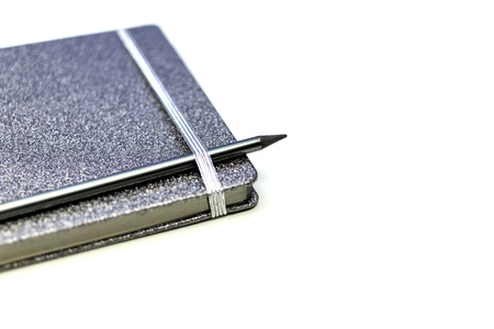 Notebook with black pencil on white desk. office supplies or education concept.