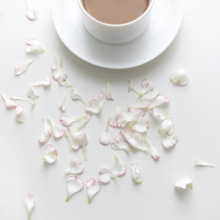 A white cup of coffee with carnation petals on white background. flat lay. Top view.