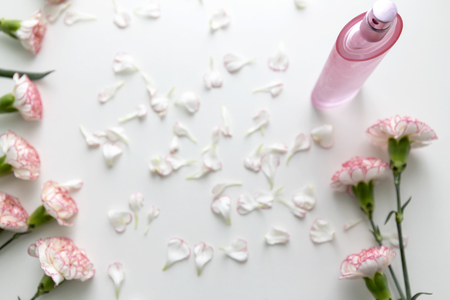 A Pink perfume bottle with pink and white carnation flowers and petals. Flat lay, top view.