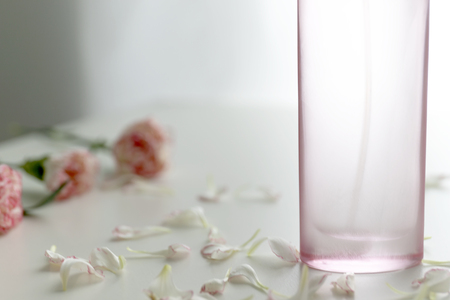 A Pink perfume bottle with pink and white carnation flowers and petals.