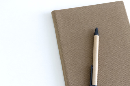 Top view of brown notebook and a pen on white desk background.