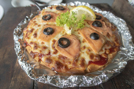 Smoked salmon pizza on wooden table.