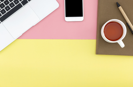 Flat lay of smart phone, laptop, notebook, pen and a cup of coffee with copy space on pastel yellow and pink background. Stock Photo