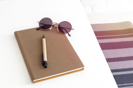 Top view of a notebook, pen and sunglasses on white table.