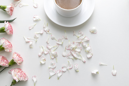 Flat lay of Coffee in white cup with pink and white carnation flowers and petals on white desk. Top view.